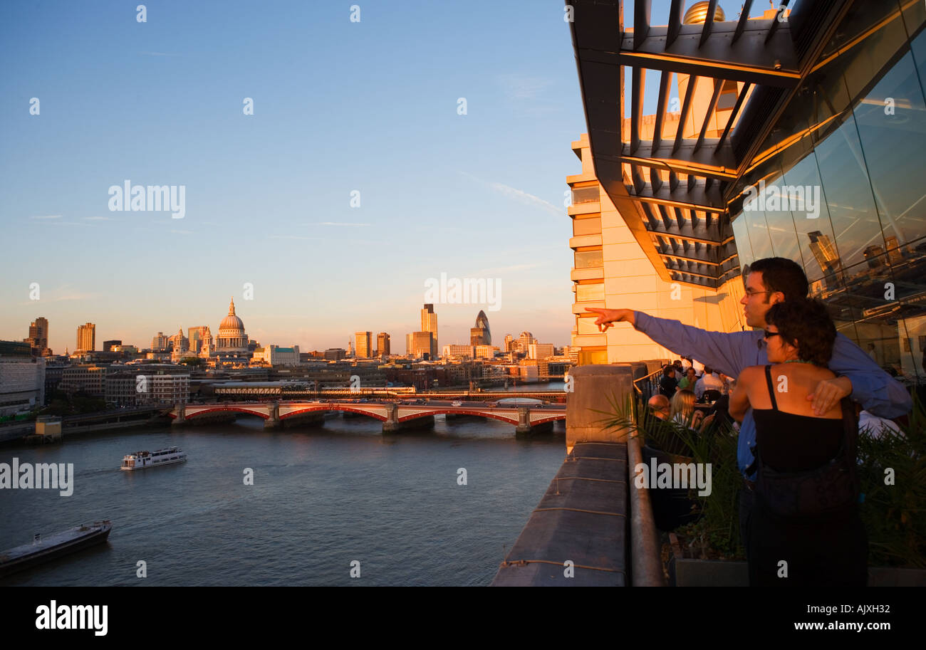 UK London Couple looking out over the river thames to st Pauls and the City Skyline - Stock Image