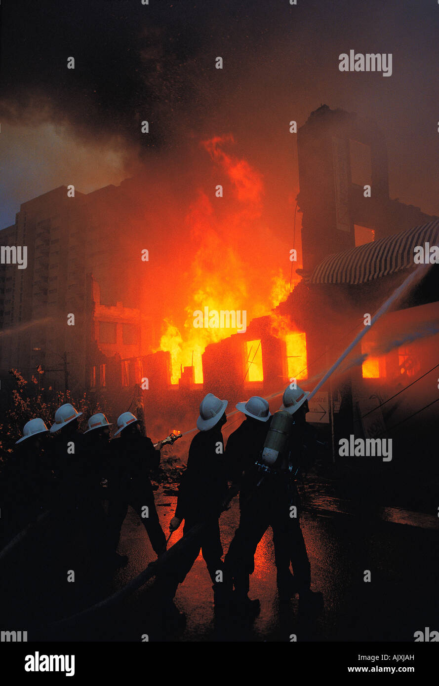 Accident & disaster. Fire fighters fighting intense fire in factory building. - Stock Image