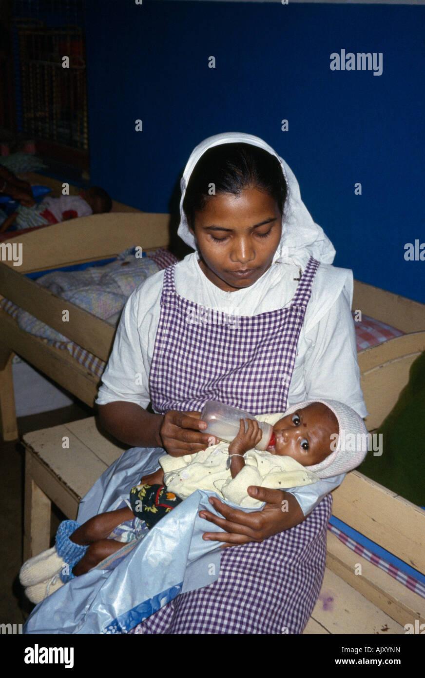calcutta india marasmus mother theresas childrens home nurse undernourished baby 18 months bottle feeding stock