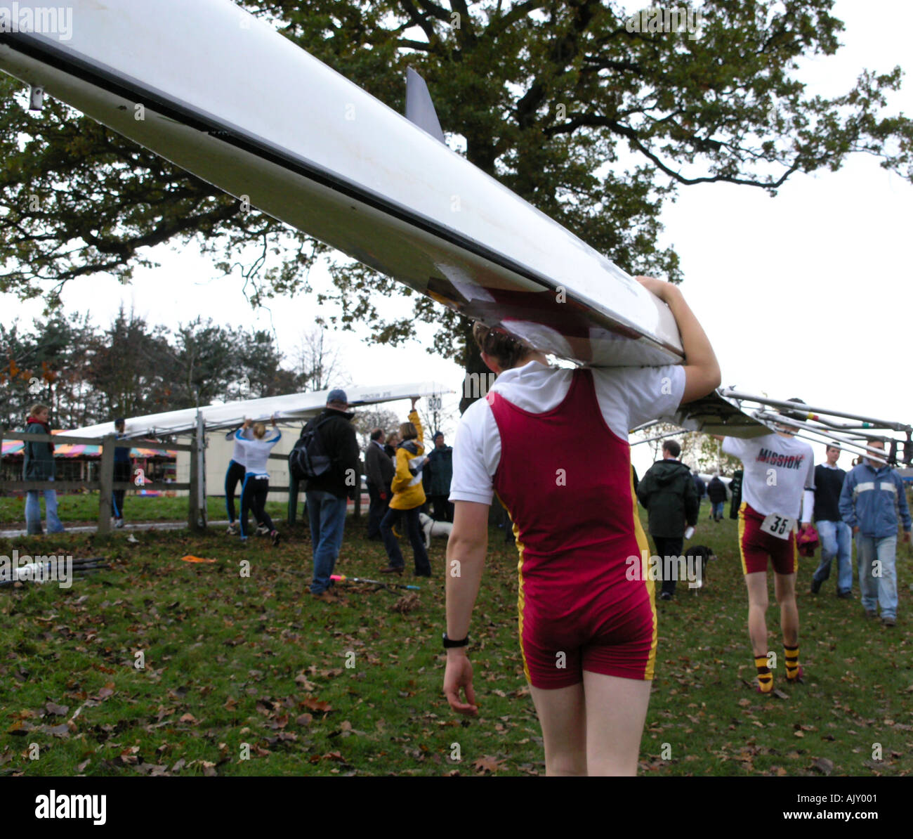 youth carrying a skiff at a regatta on the River Thames - Stock Image