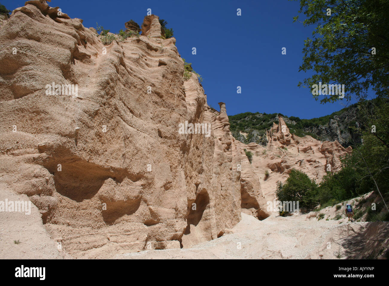 Walker exploring the spectacular Lame Rosse eroded rock formation near Fiastra lake and dam, Sibillini National - Stock Image