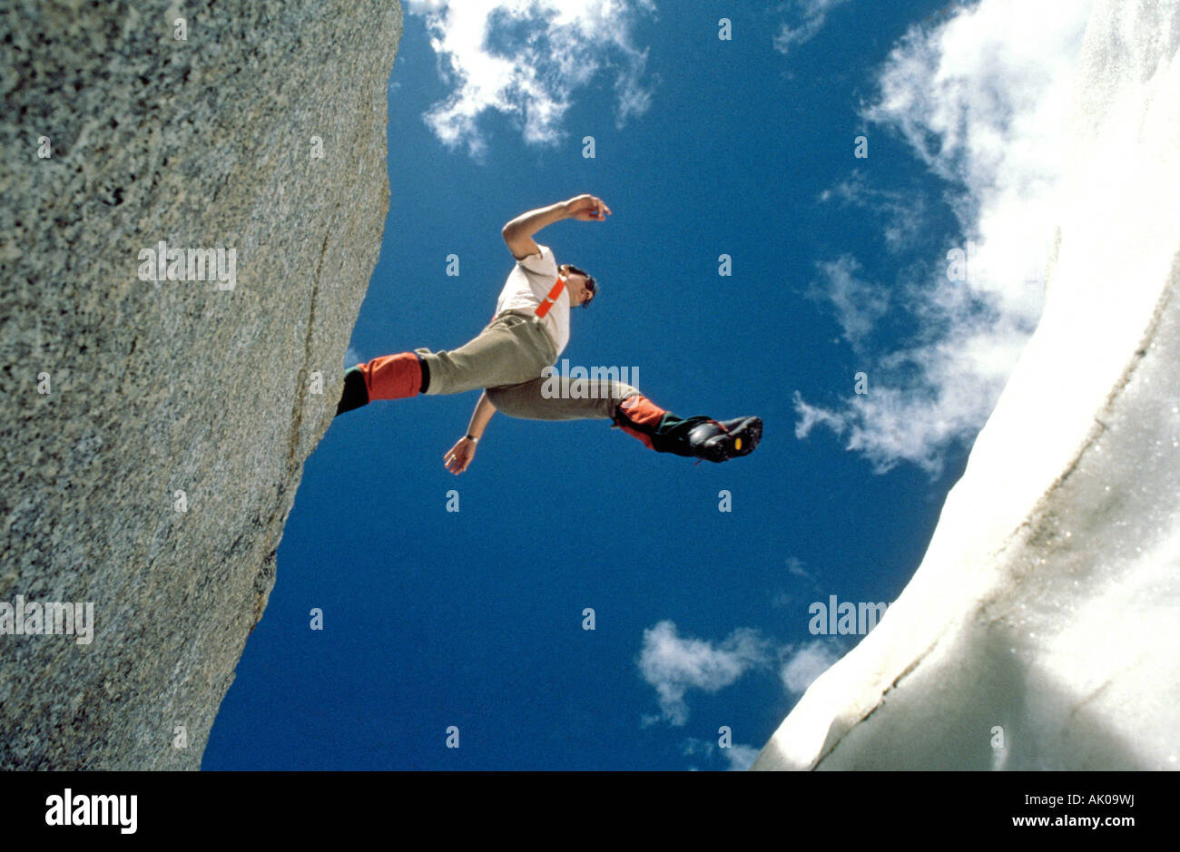 A hiker jumps over a crevasse on a glacier high in the
