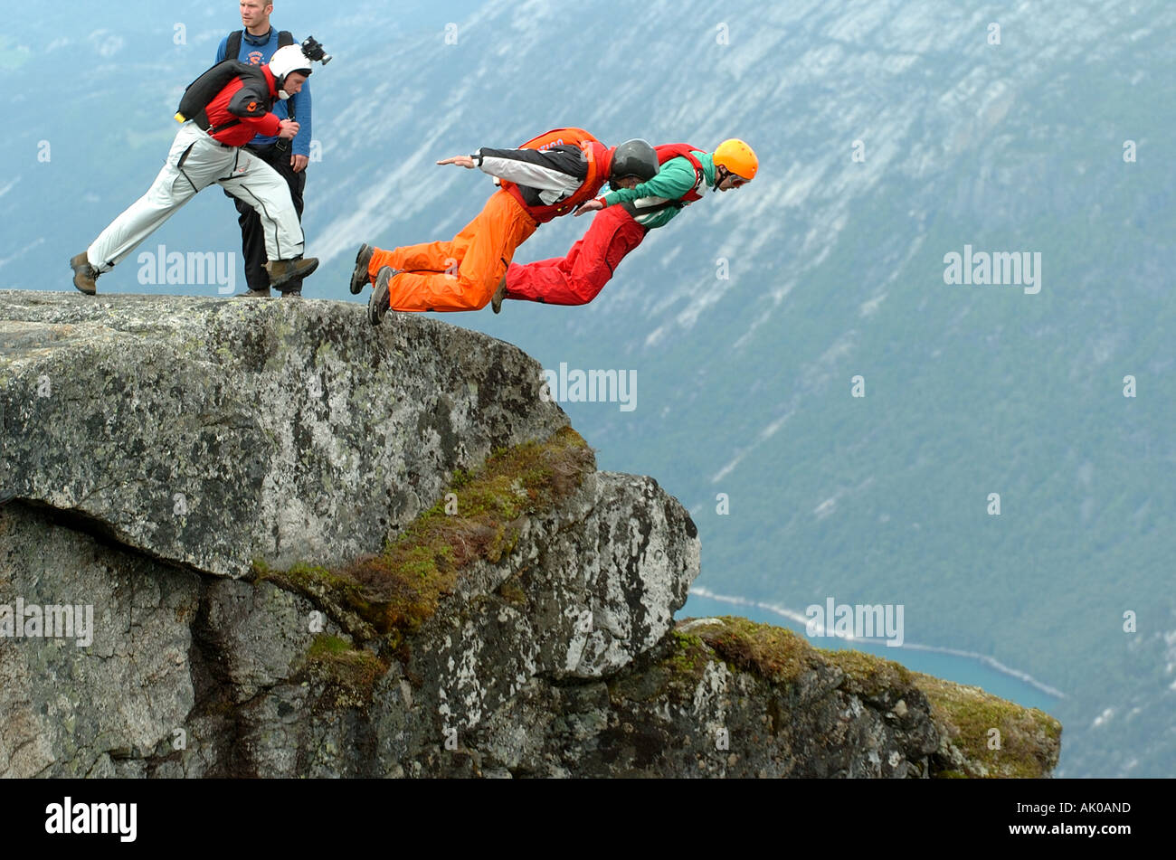 BASE jumpers taking off big cliff in a fjord in Norway - Stock Image