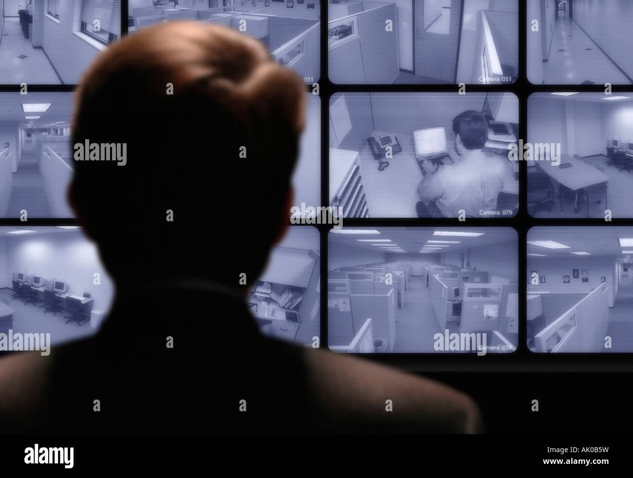 Video surveillance Man watching an employee work via a closed circuit video monitor - Stock Image