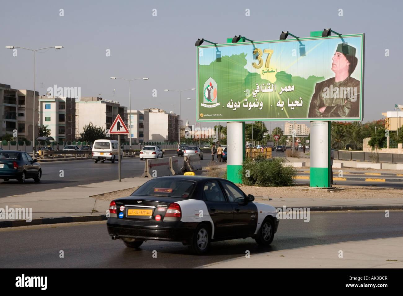 Tripoli, Libya. Street Scene, Qadhafi Billboard, 37th Anniversary of the Revolution, Taxi - Stock Image