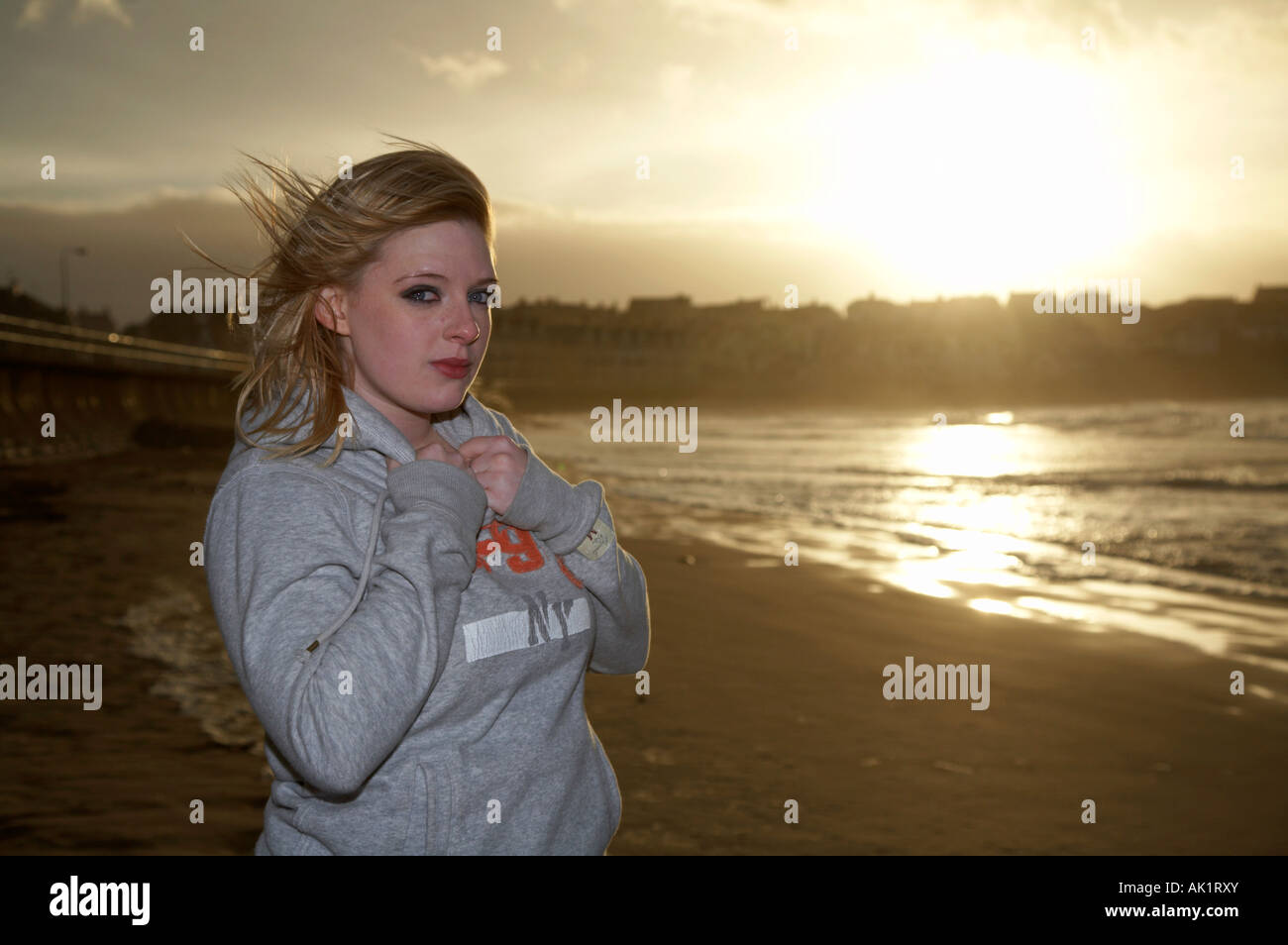 blonde haired female student with tears in her eyes standing on a beach at sunset wearing a sweatshirt holding it - Stock Image