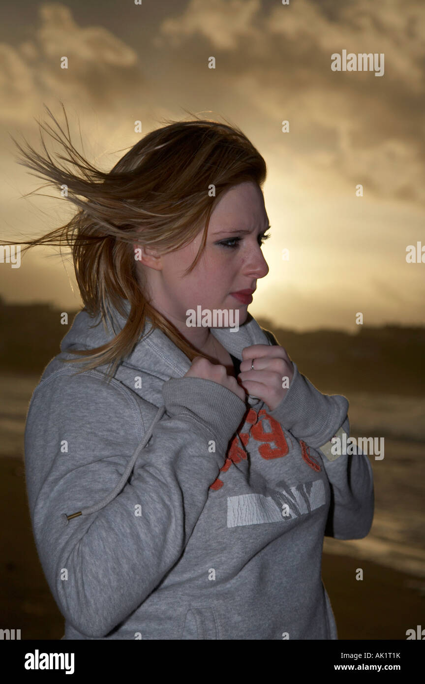 female student standing on a beach at sunset with tears in her eyes and hair blowing in the wind hands holding her - Stock Image