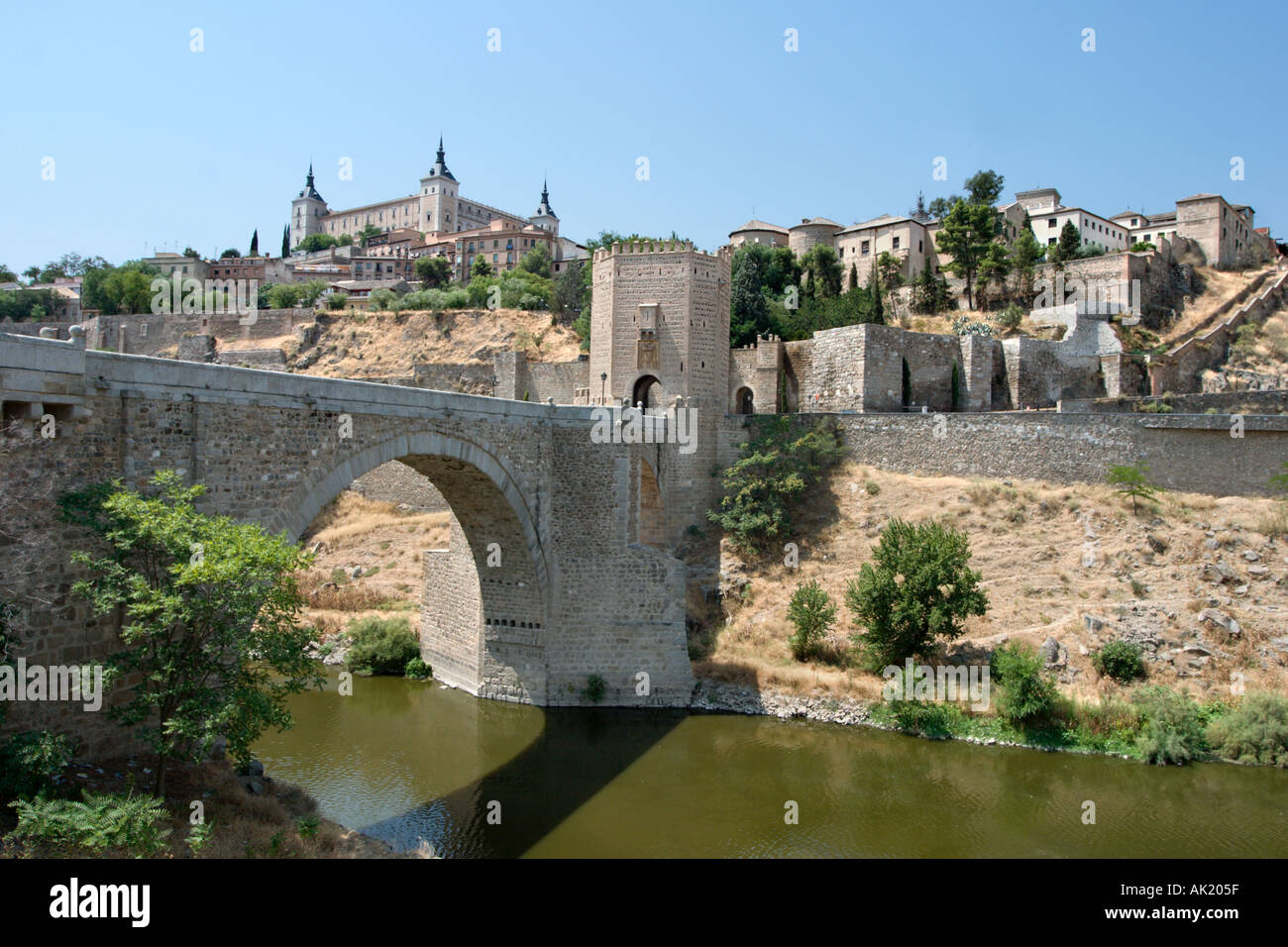The Puerta de Alcantara on a bridge over the River Tagus with the Alcazar behind, Toledo, Castilla-La-Mancha, Spain - Stock Image