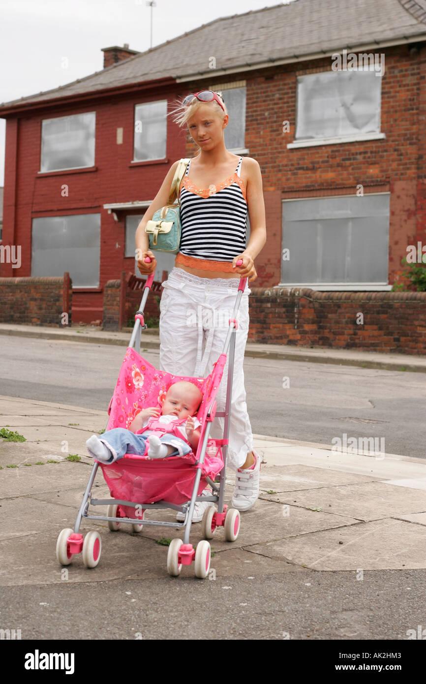 Teenage Mum Pushing Buggy In Run Down Derelict Area