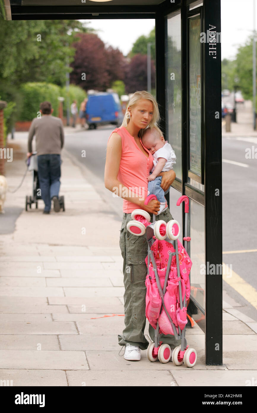 Teenage Mum At Bus Stop With Baby And Buggy