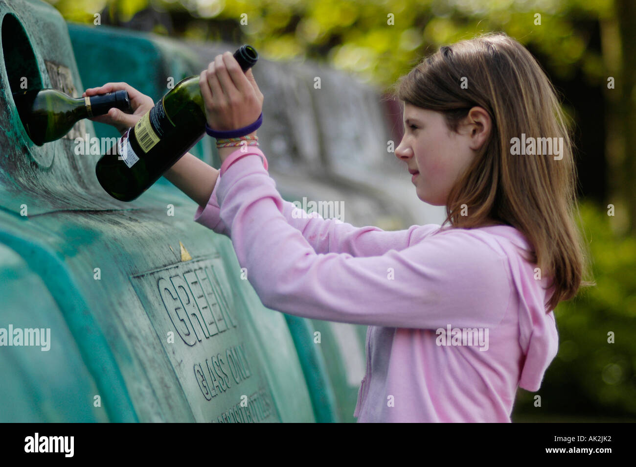 girl recycling at bottle bank - Stock Image