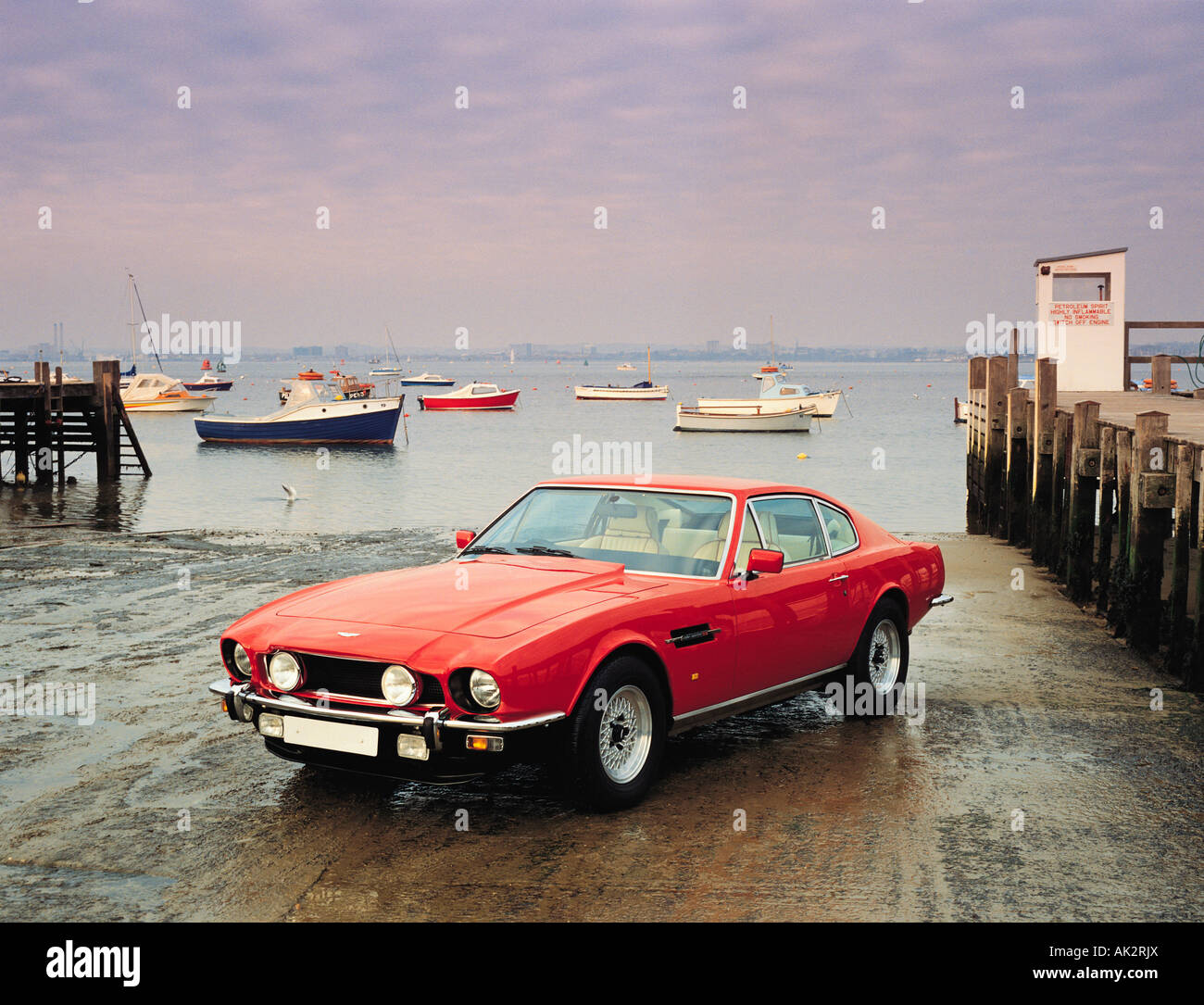Red Aston Martin Dbs Sports Car On Harbour Slipway With Boats In