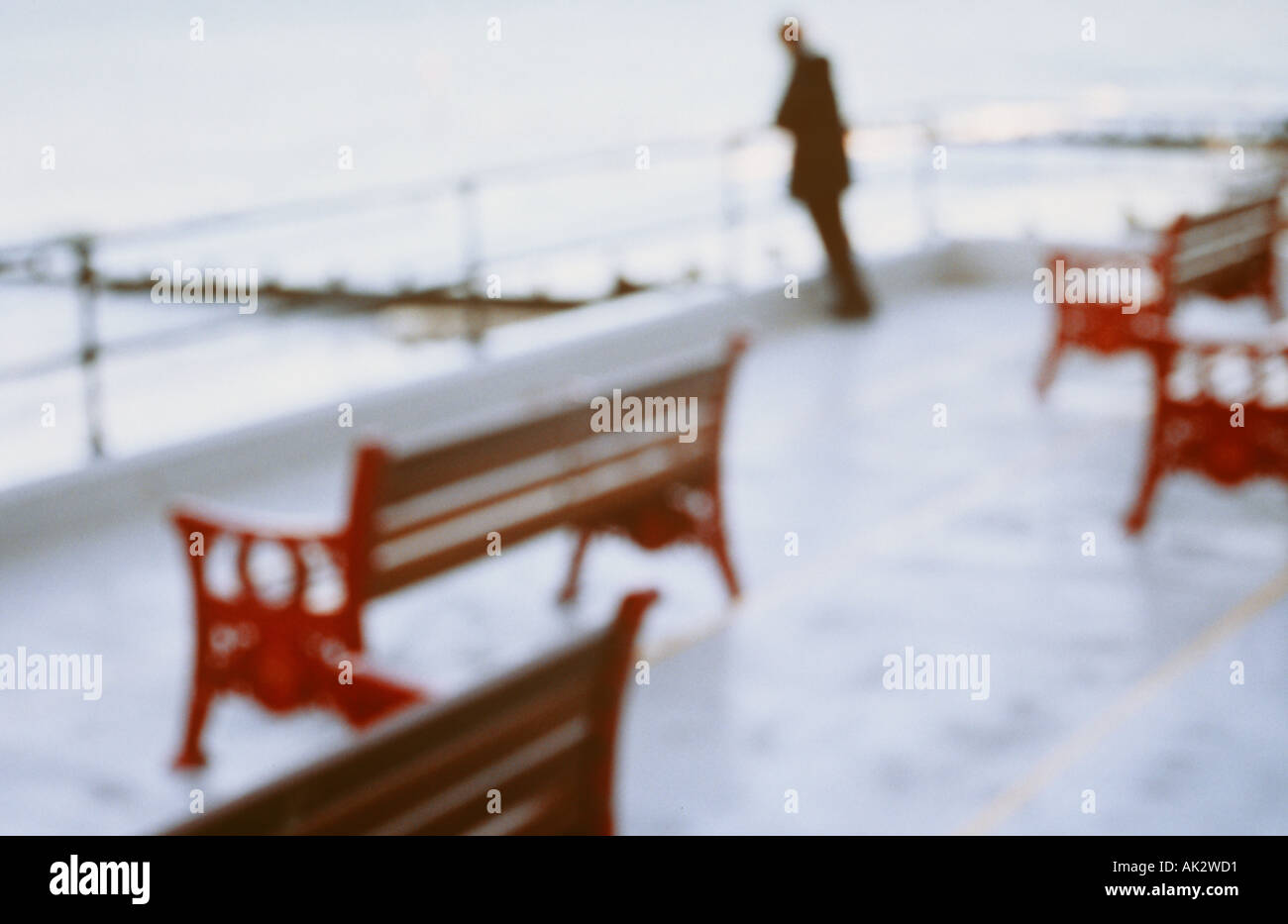Impressionistic solitary figure leaning on railings surrounding empty bench seats and gazing out at a calm winter sea - Stock Image