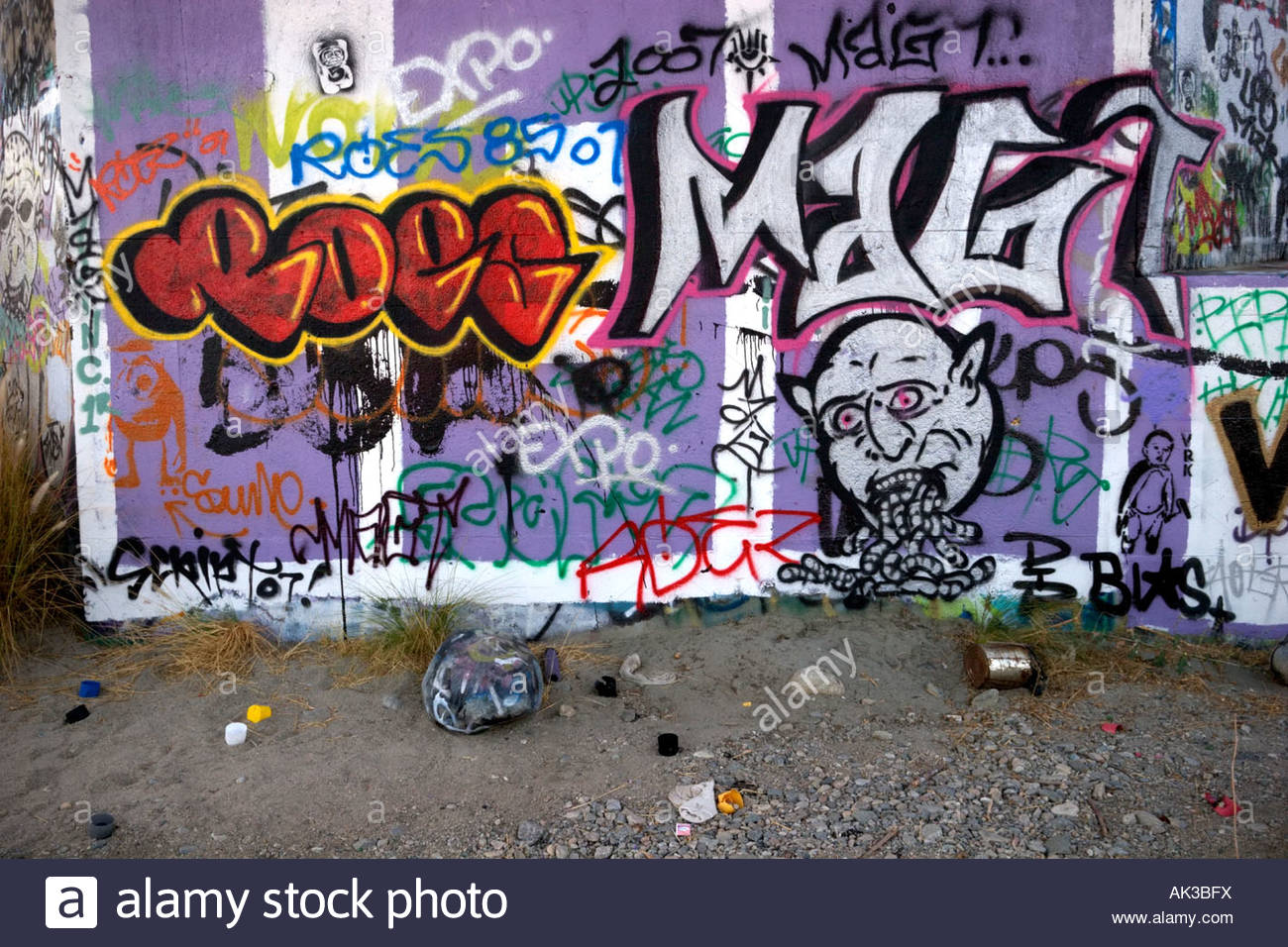 Gang Graffiti on Wall and Spray Paint Cans along the San Gabriel River California - Stock Image