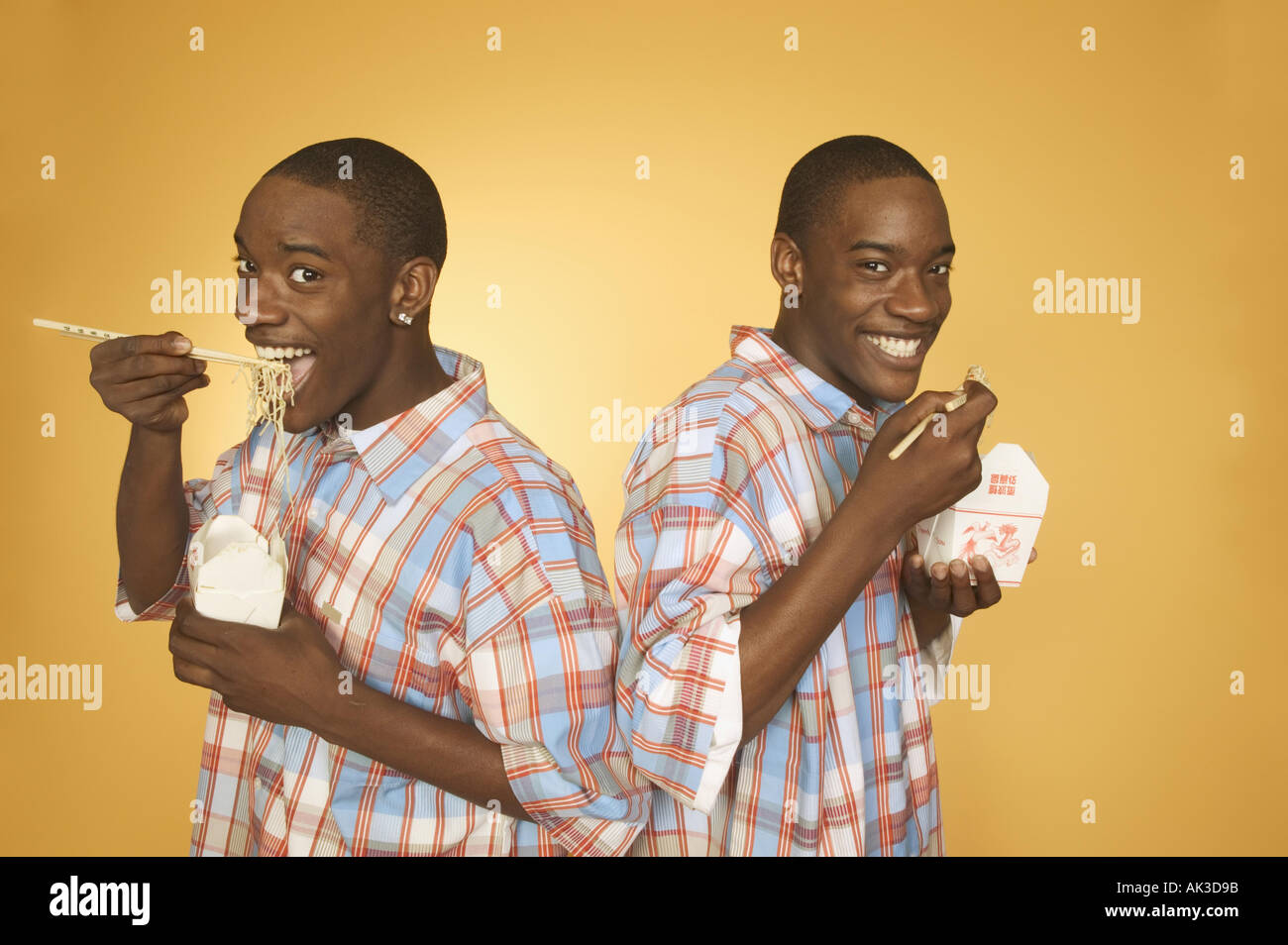 Twin teenage african american boys eating noodles from cartons