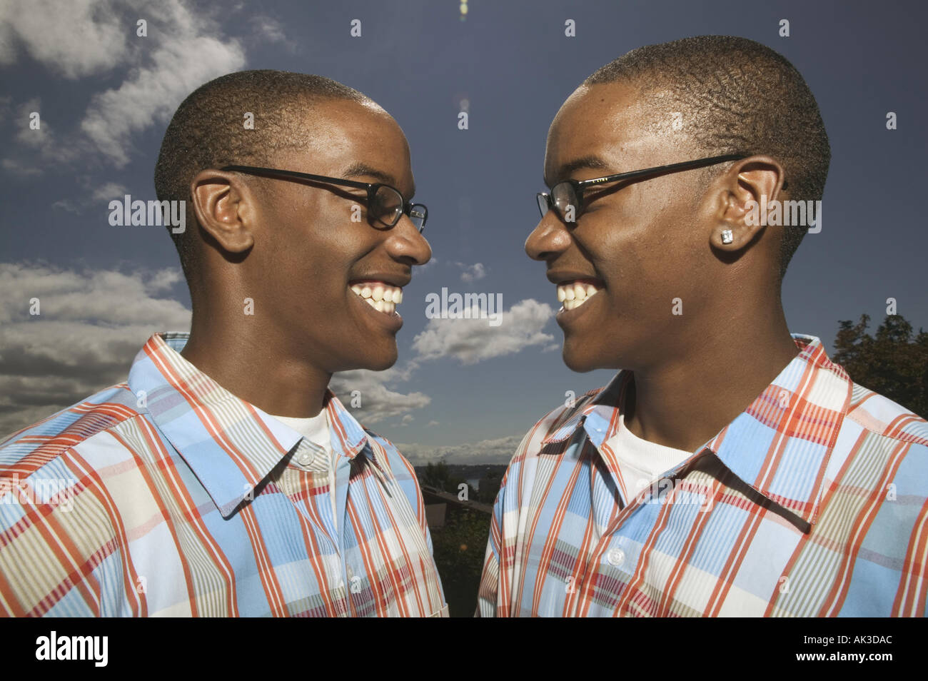 Outdoors portrait of twin african american teenage boys in glasses and matching plaid shirts