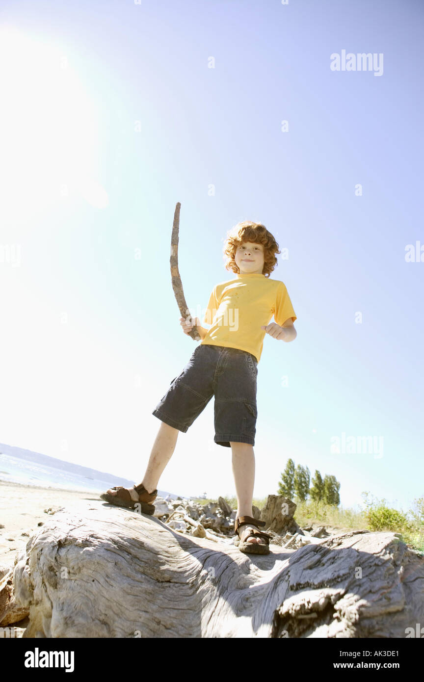 Young red headed boy holding a stick - Stock Image