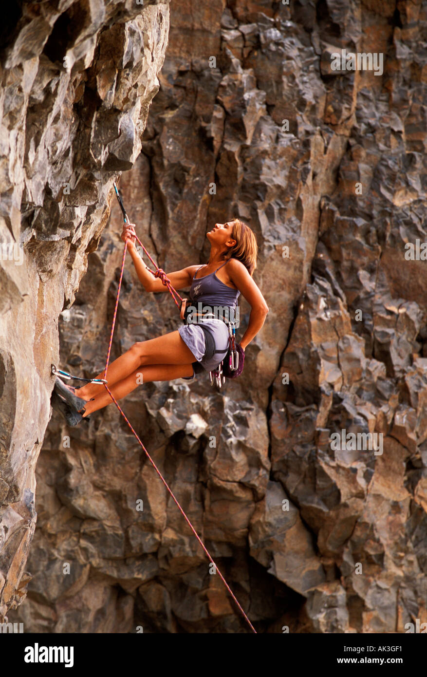 A young woman rock climber pauses during an ascent of a vertical basalt wall - Stock Image