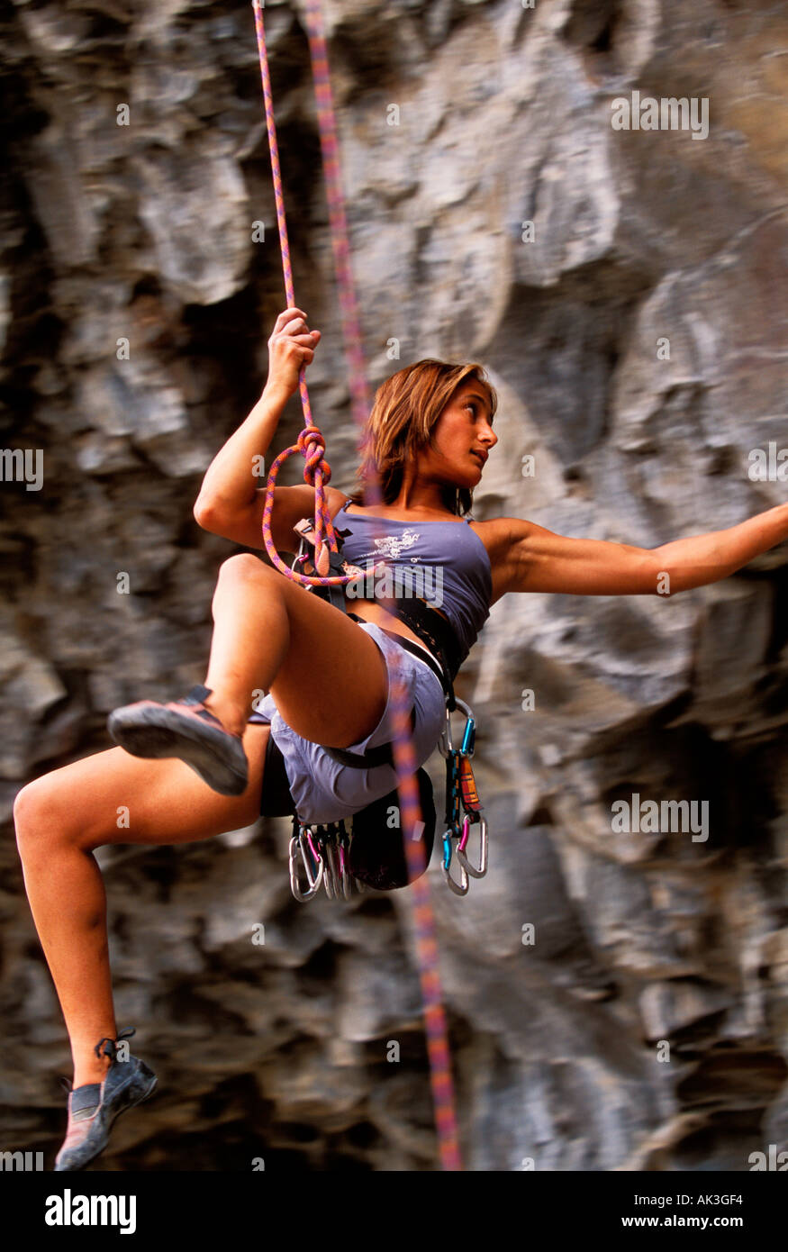 A young woman climber swings on the end of a rope to a differenct location on a basalt wall - Stock Image
