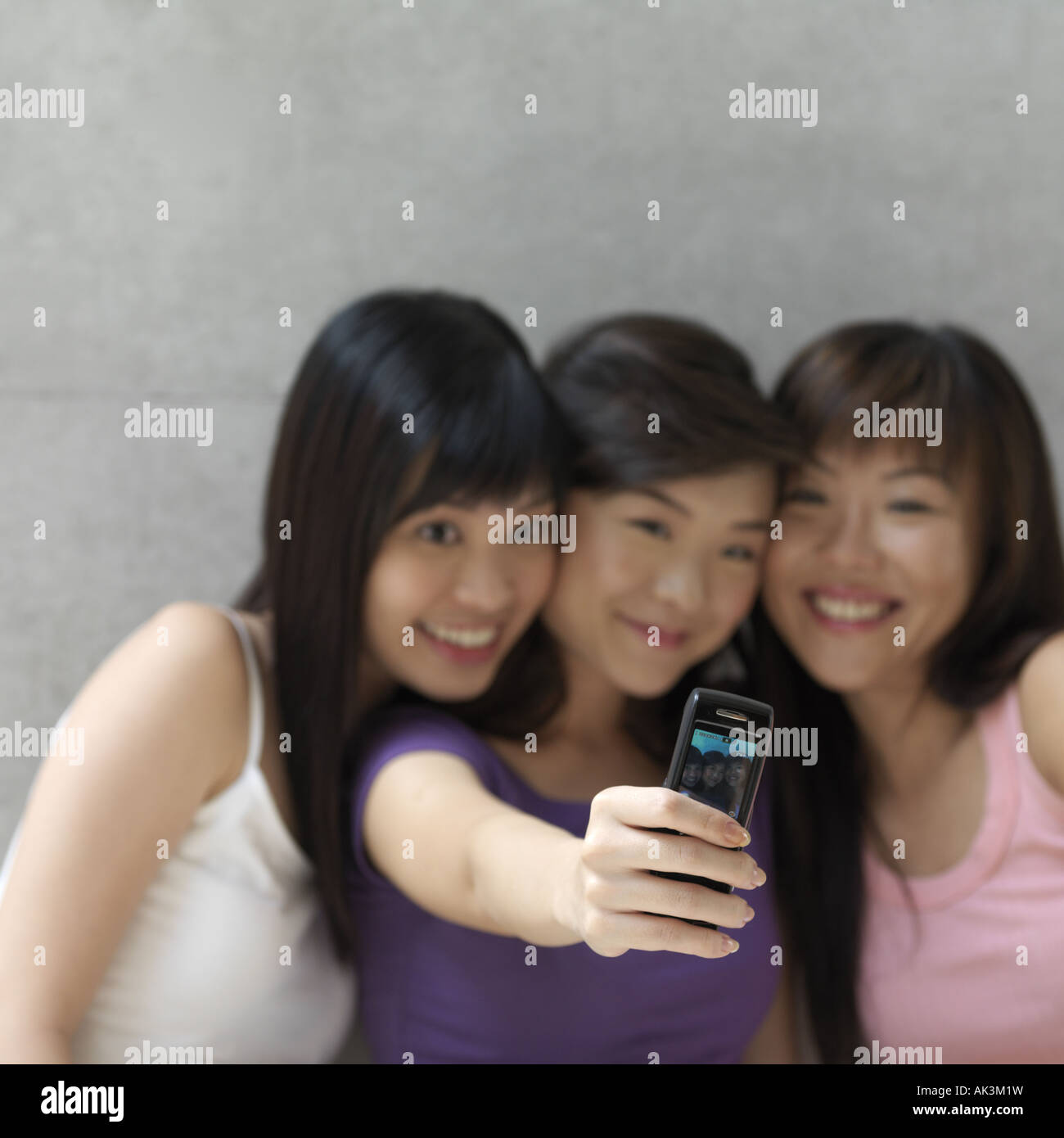 Three women taking photo of themselves with mobile phone, smiling - Stock Image