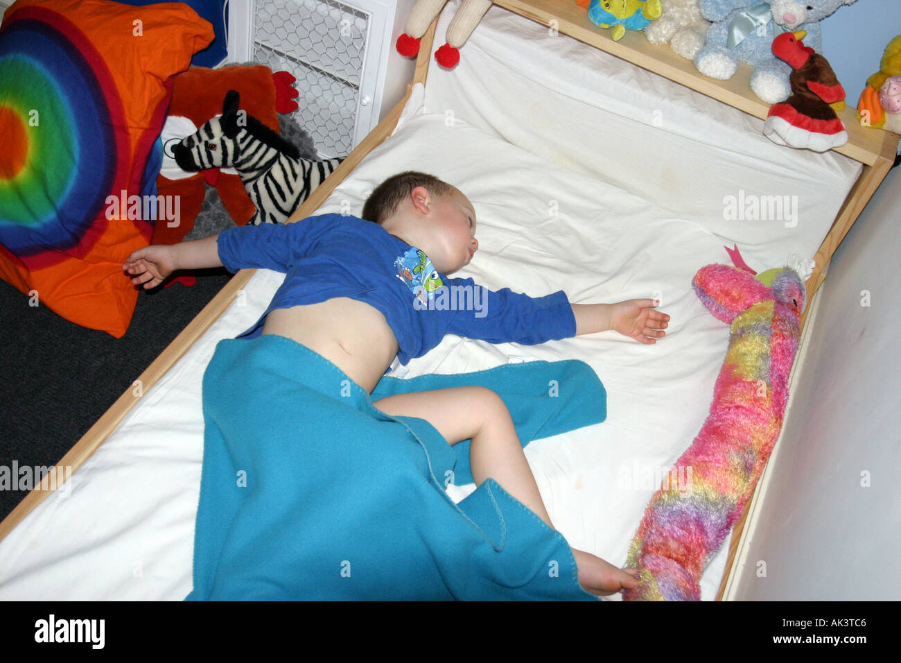 Young child sleeping in bed with blankets falling off Stock Photo