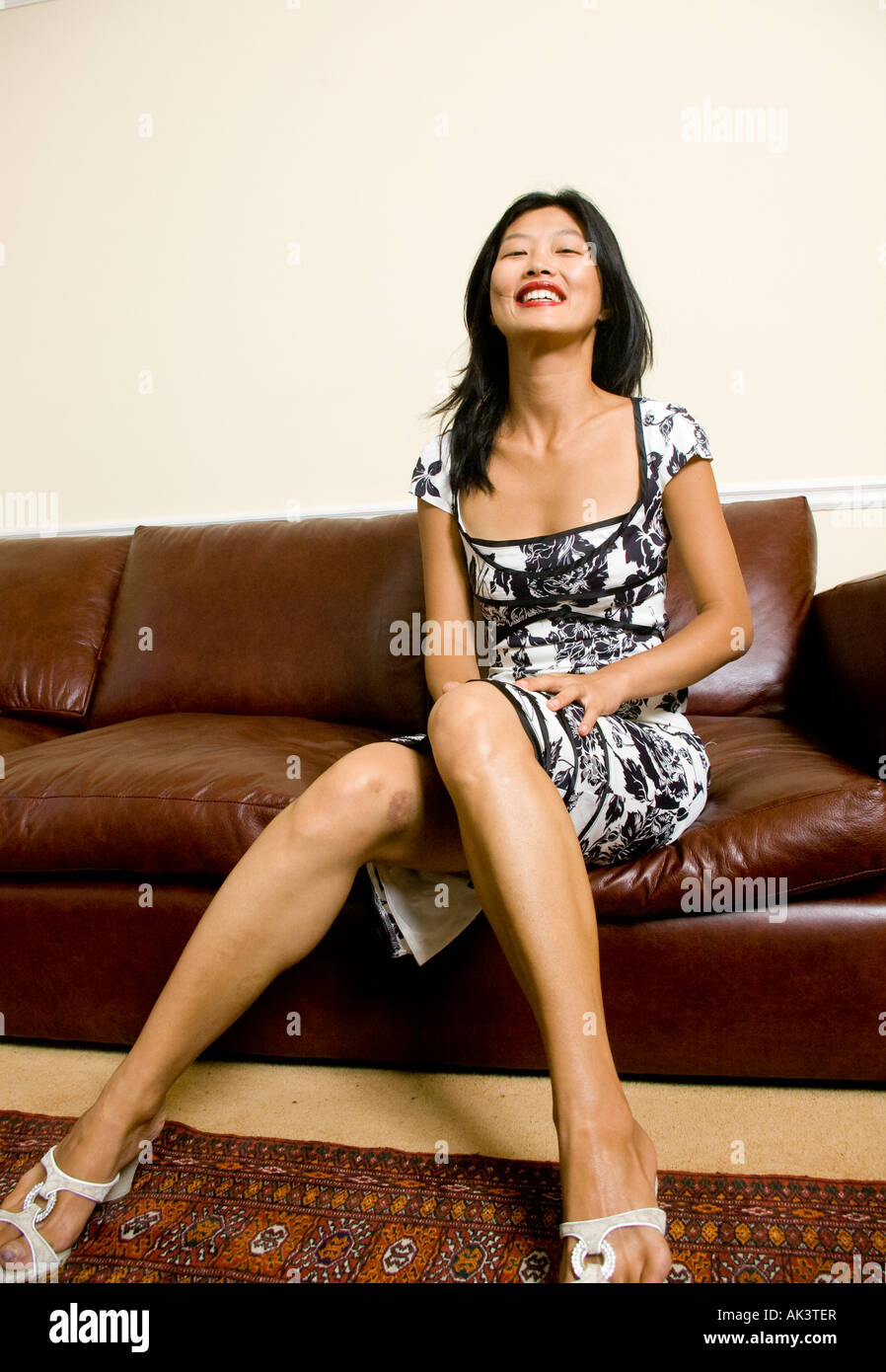 korean asian woman in formal dress sitting on leather sofa revealing