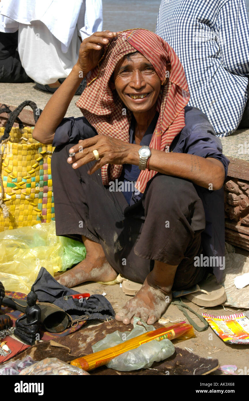 Man selling small souvenirs wearing a kerchief smoking a joint Water Festival Phnom Penh Cambodia Stock Photo