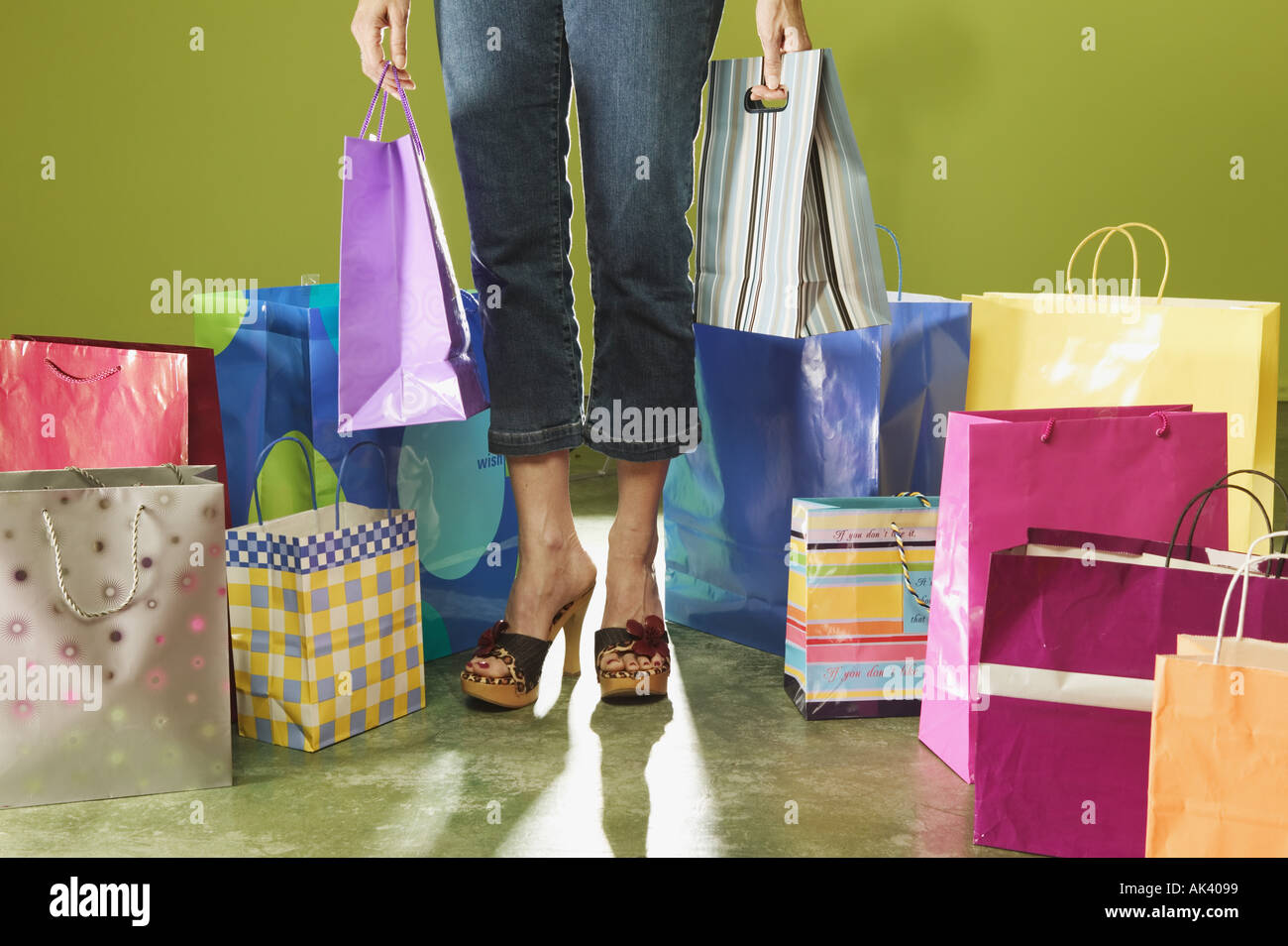 Cropped image of a woman standing among shopping bags - Stock Image
