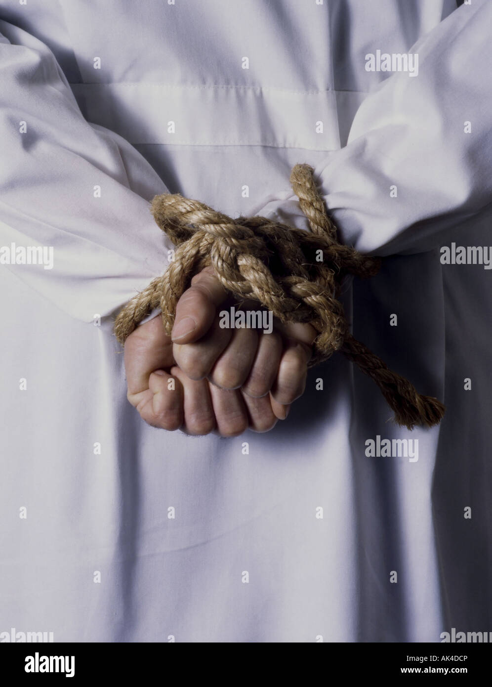 doctor with hands tied behind his back - Stock Image
