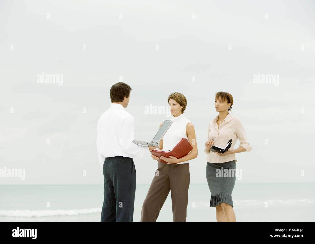 Businessman with laptop facing women with agendas, on beach Stock Photo