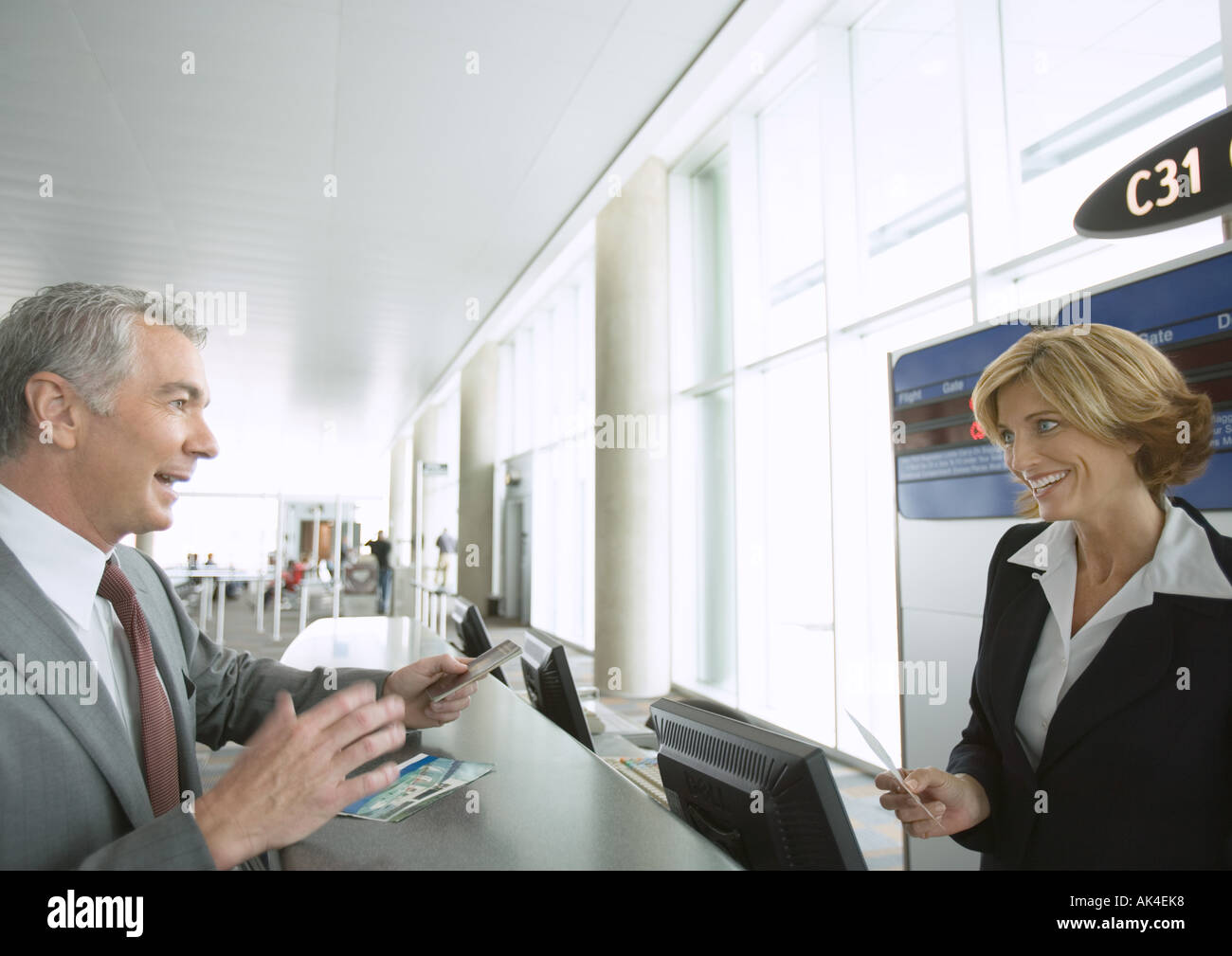 Businessman at airline check-in counter - Stock Image