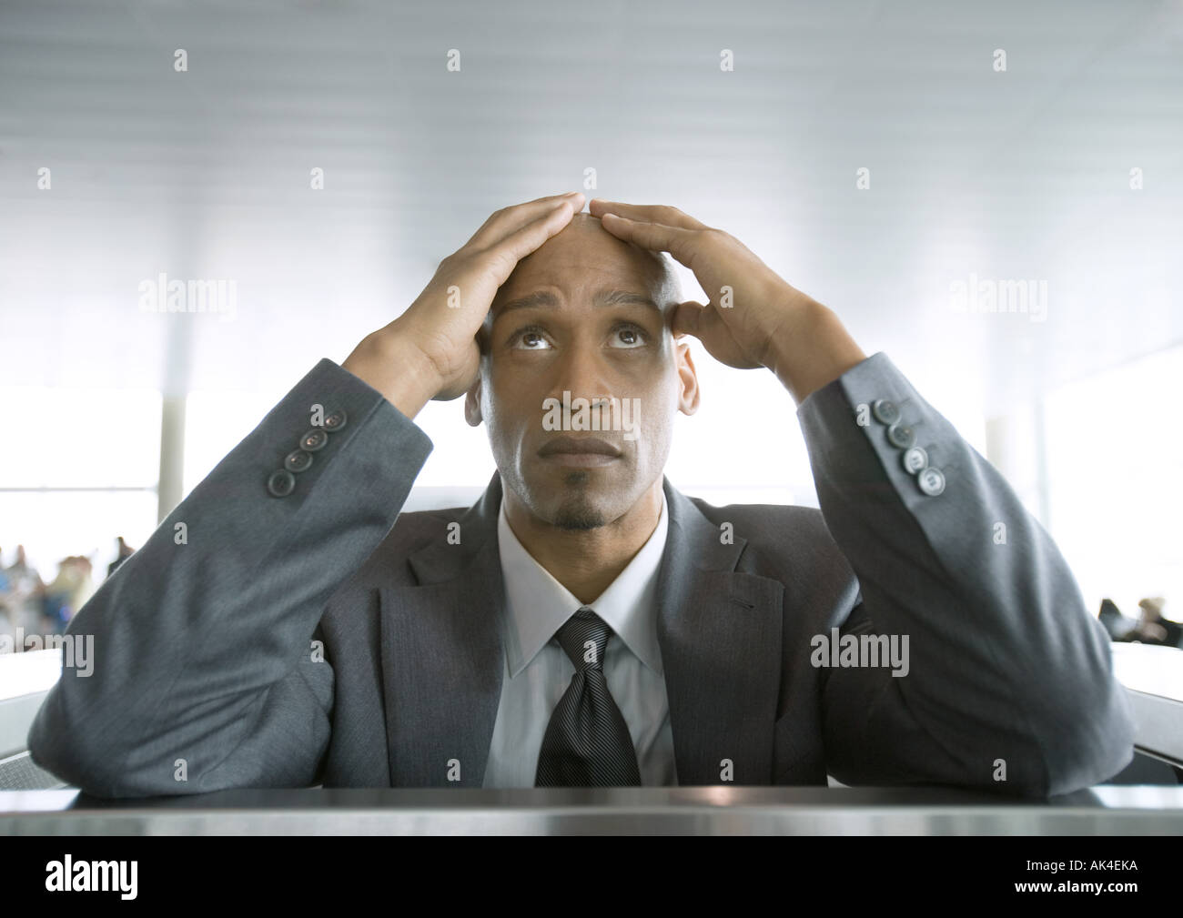 Businessman looking up and holding head in airport - Stock Image