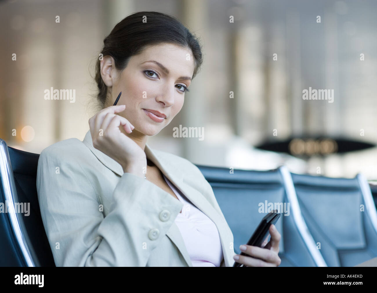 Businesswoman using electronic organizer in airport lounge, smiling at camera - Stock Image