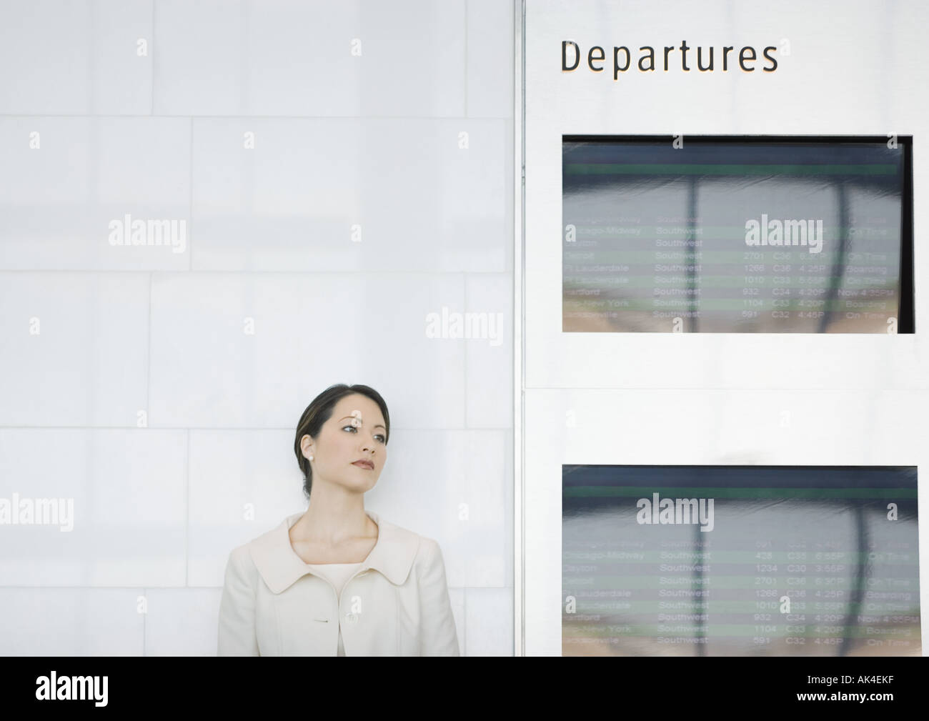 Woman leaning against wall by departure board - Stock Image