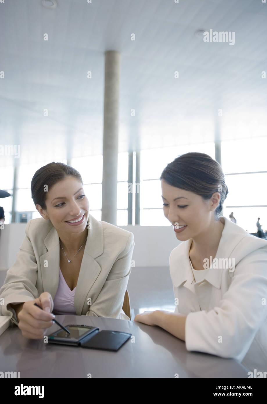 Two businesswomen using electronic organizer - Stock Image