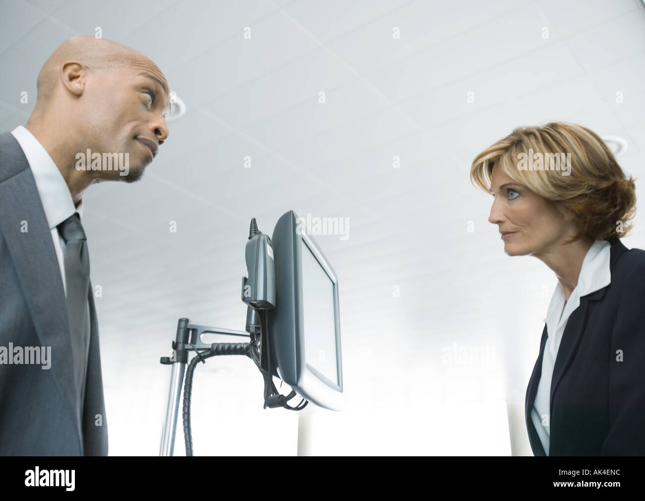 Businessman and female airline attendant staring at each other - Stock Image