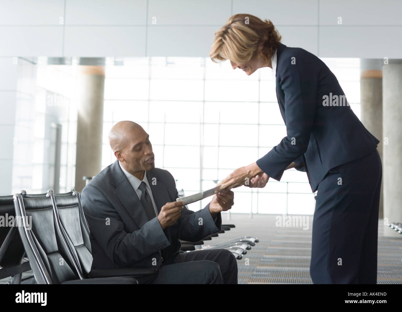 Airline attendant handing seated businessman a ticket - Stock Image
