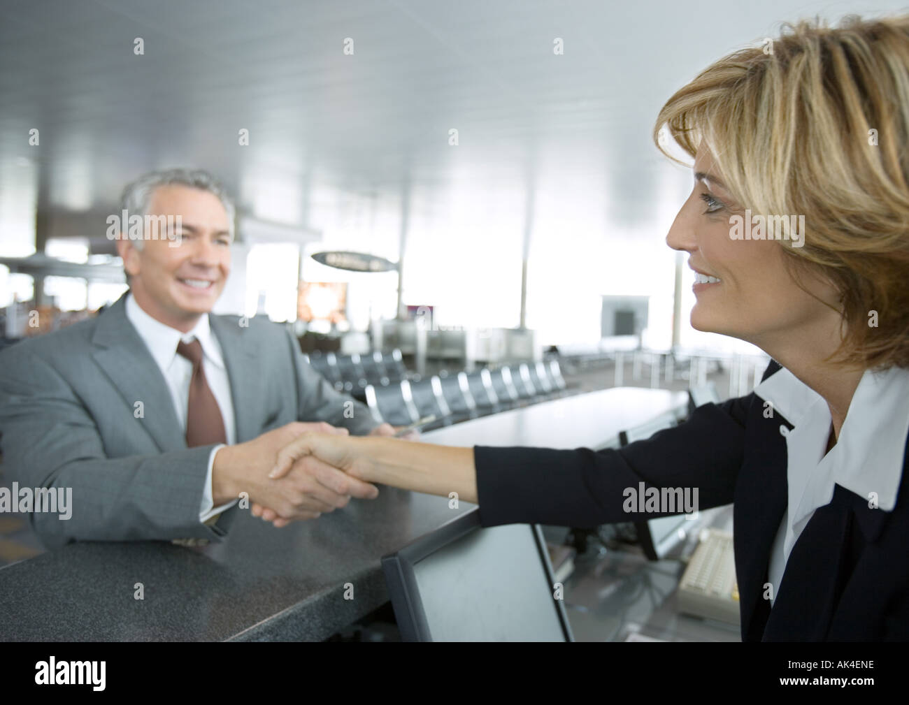 Airline attendant shaking hands with passenger - Stock Image