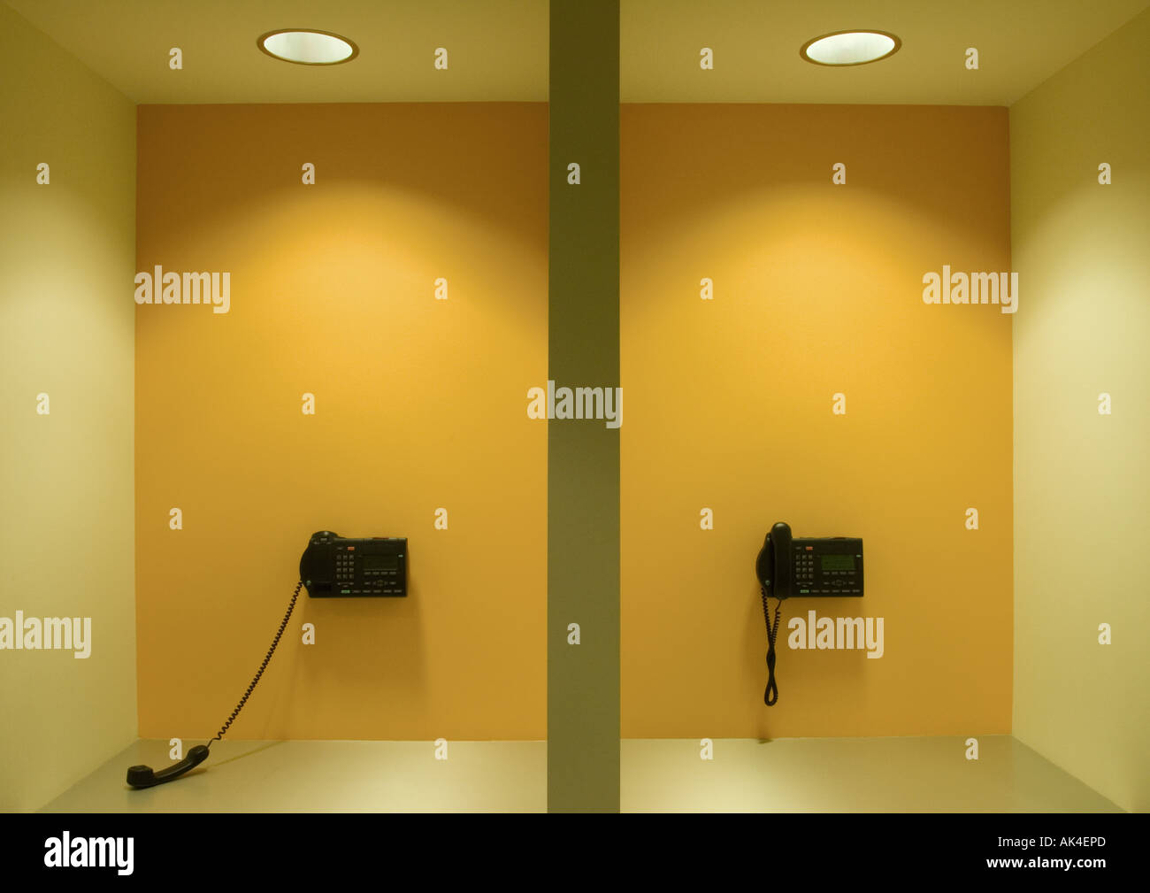 Two wall phones, one off the hook - Stock Image