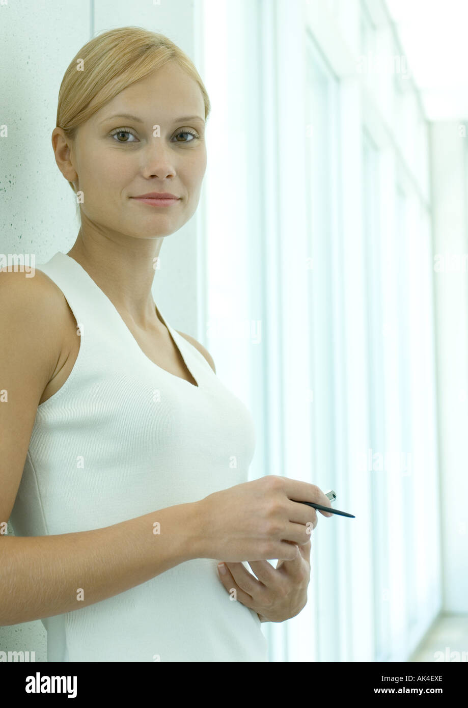 Woman standing in office space, stylus in hand - Stock Image
