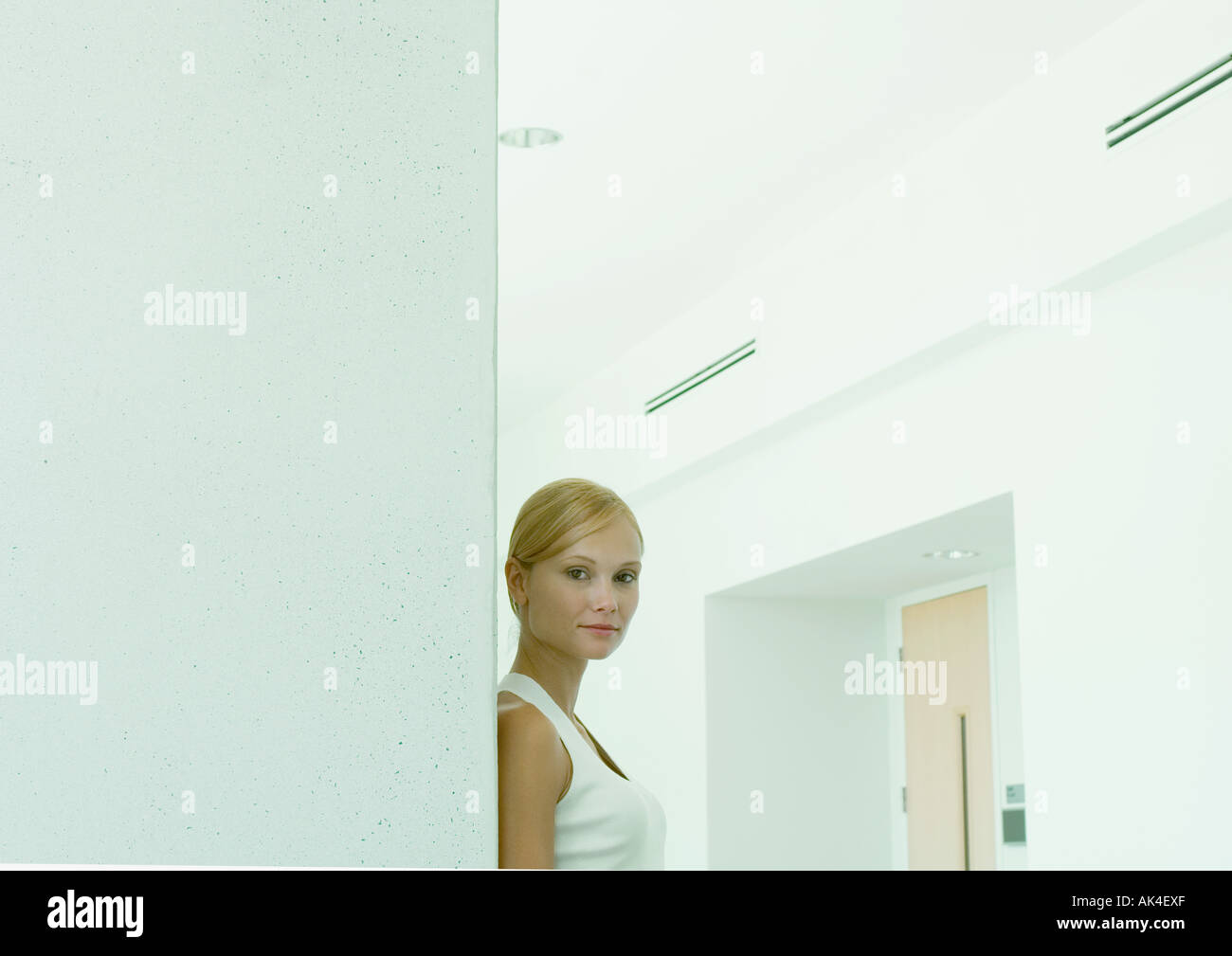 Woman standing in hallway of office building - Stock Image