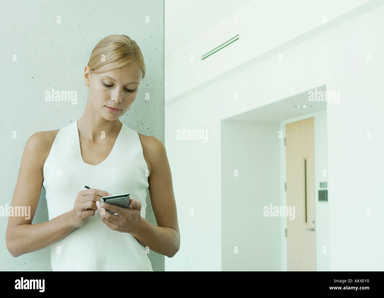Woman using electronic organizer in hallway of office building - Stock Image