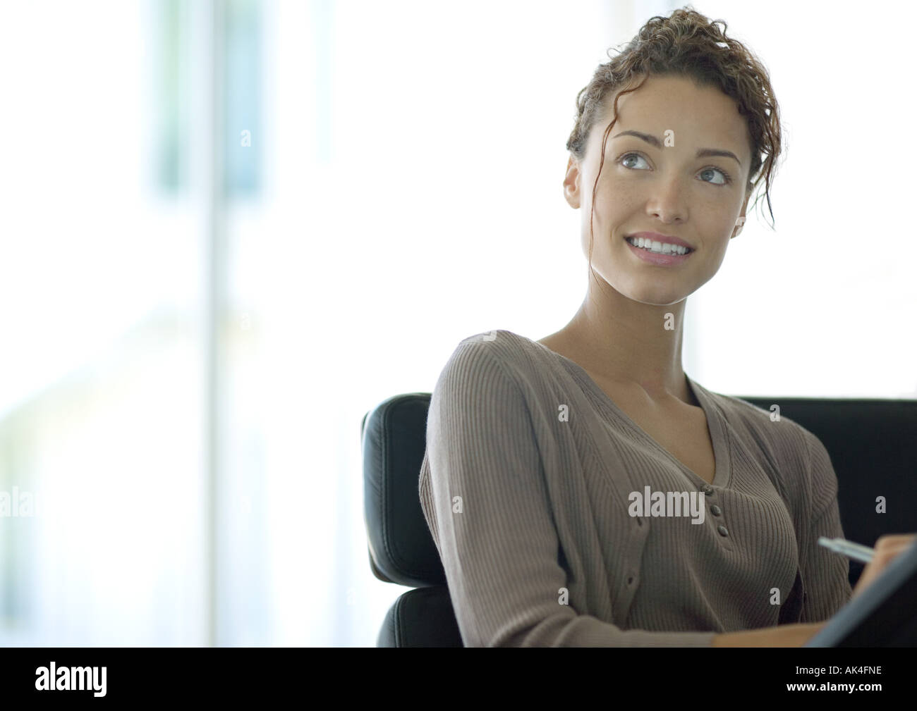Woman writing and looking up - Stock Image