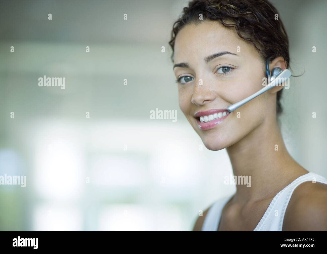 Woman wearing headset and smiling - Stock Image