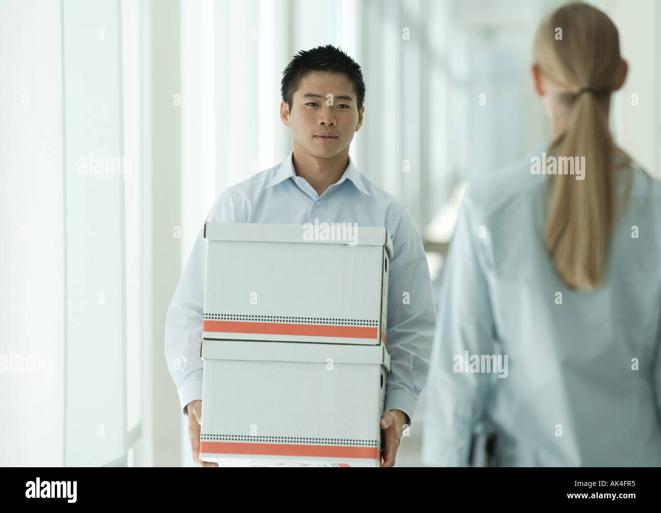Office worker carrying boxes through corridor - Stock Image