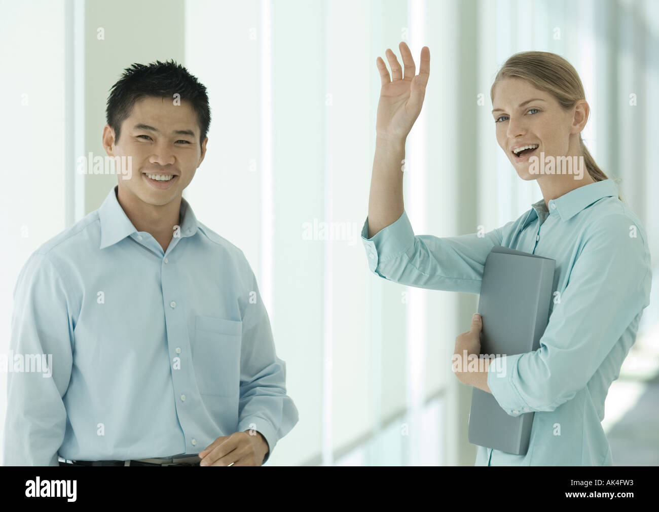 Office workers smiling and waving to camera - Stock Image