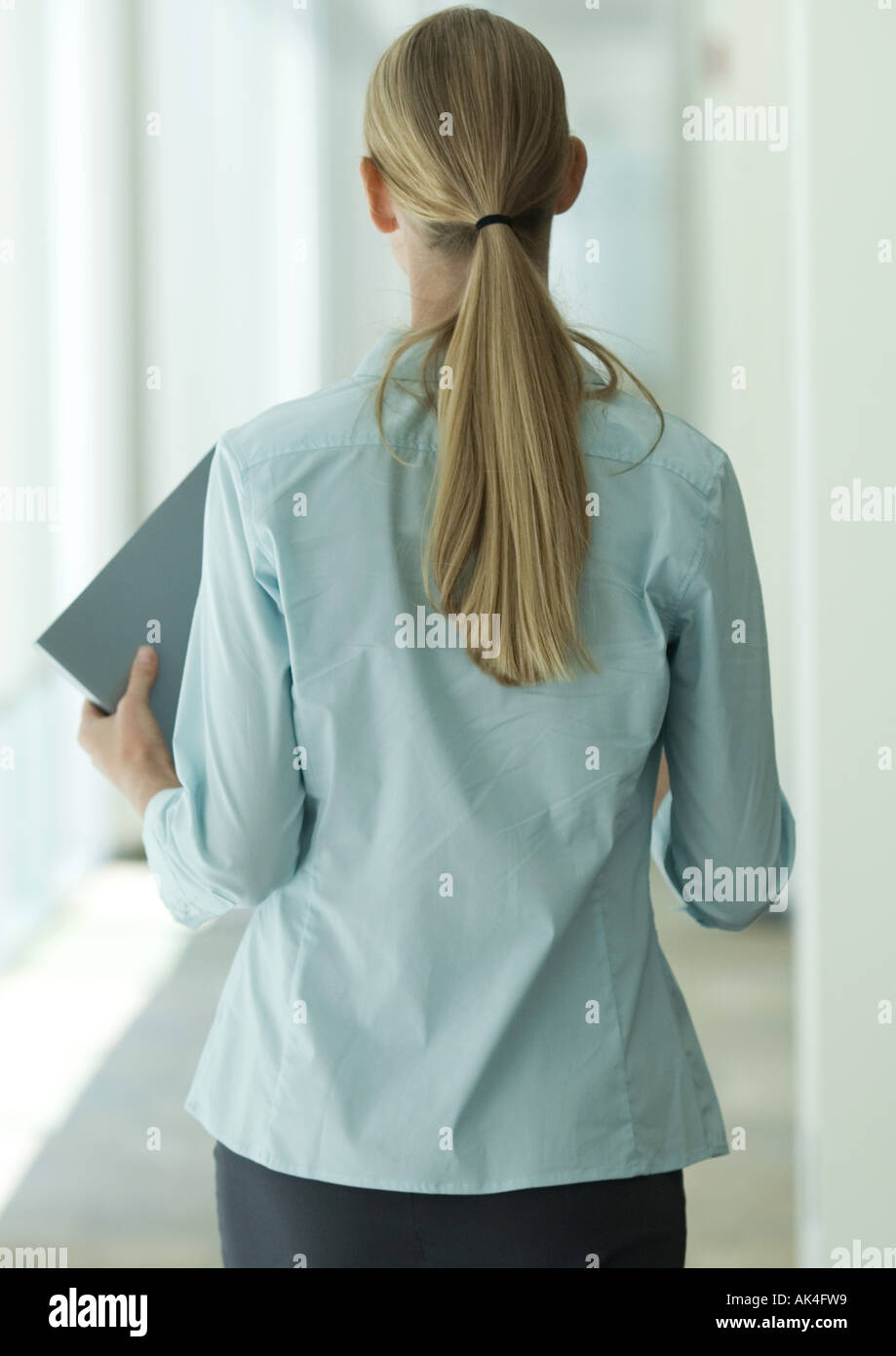 Female office worker walking through corridor, rear view - Stock Image