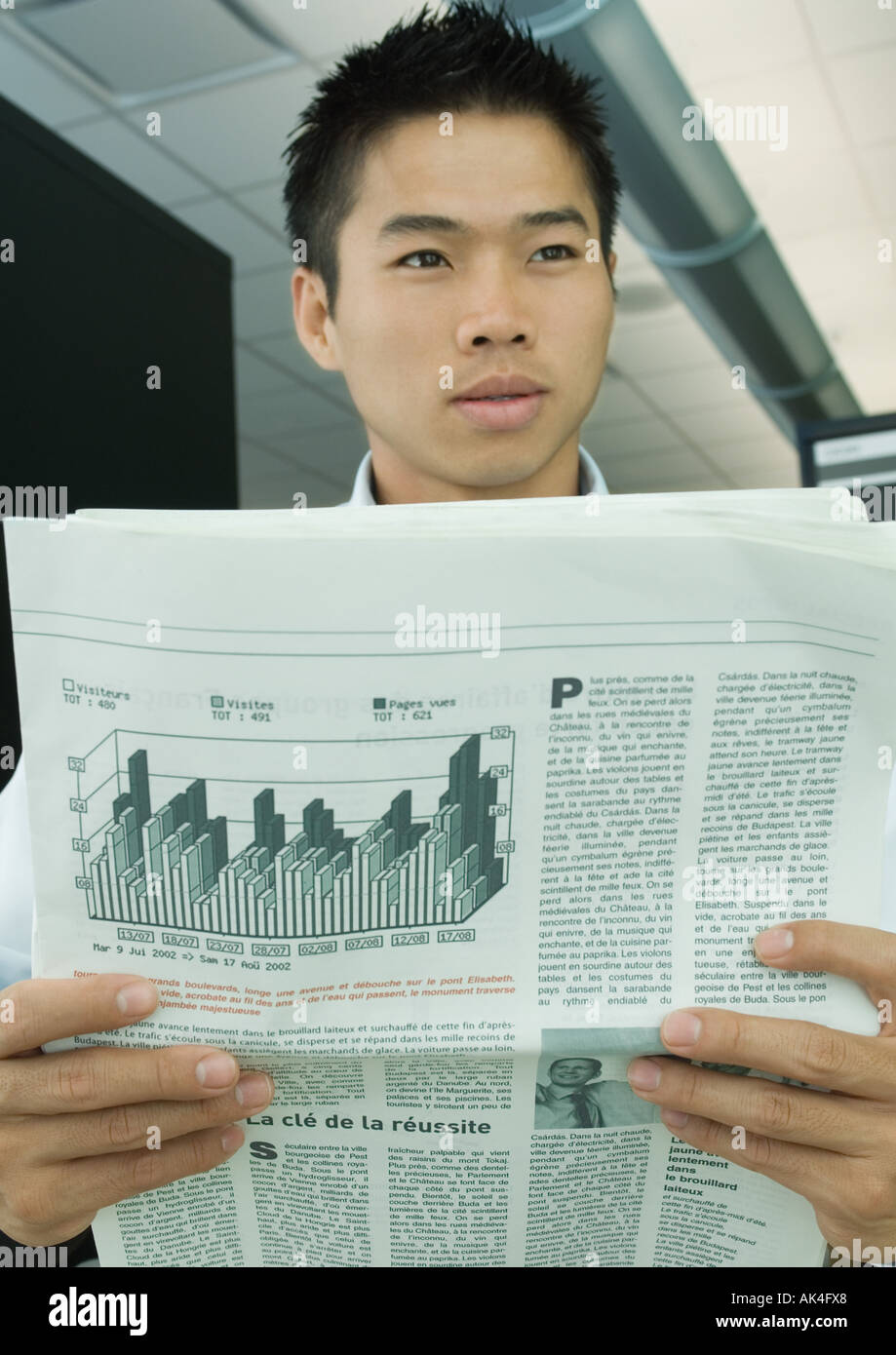 Man looking up from newspaper - Stock Image