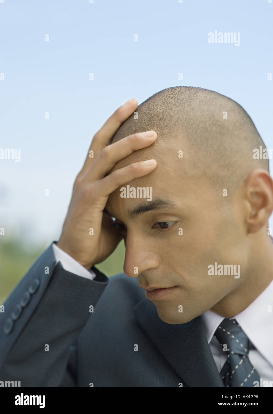 Businessman holding head - Stock Image