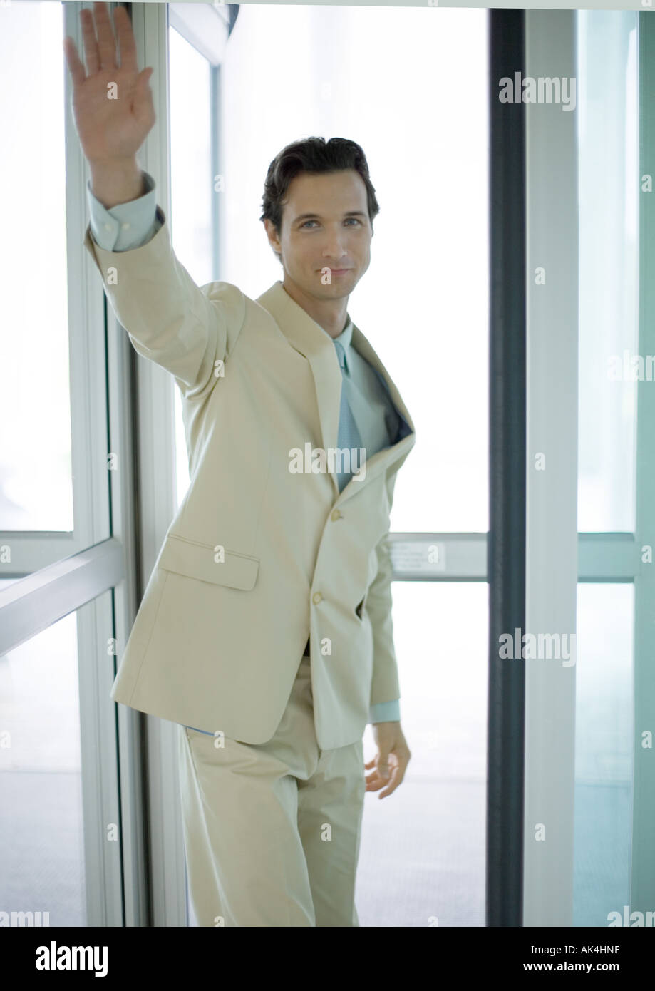 Businessman standing by door, waving - Stock Image